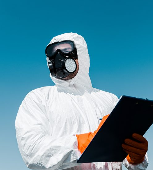 man in protective mask and uniform holding clipboard